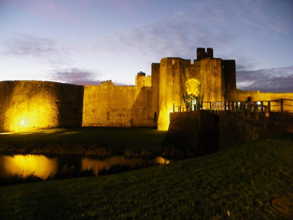 Caerphilly Castle entrance, walls and towers floodlit at night