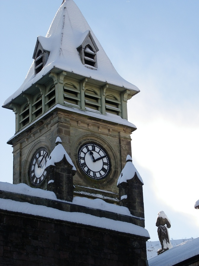 clocktower covered in snow at Craig y Nos Castle South Wales