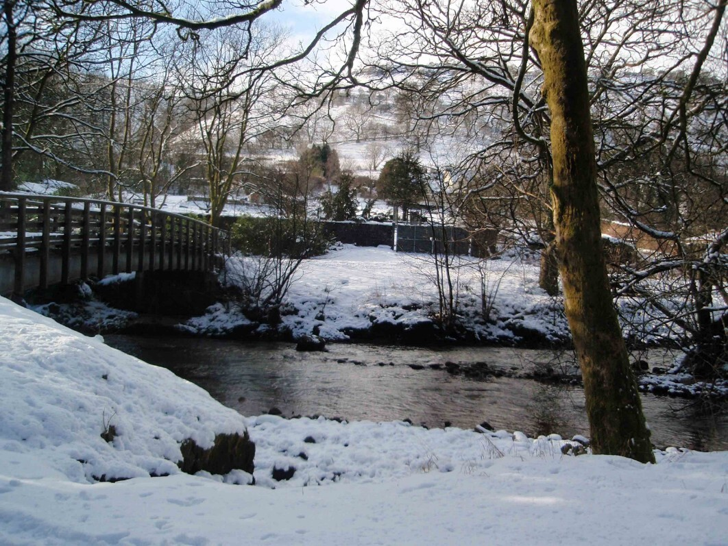 Dog Friendly Hotel Swansea Wales River Tawe and wooden bridge at Craig y Nos Country Park in Winter Snow