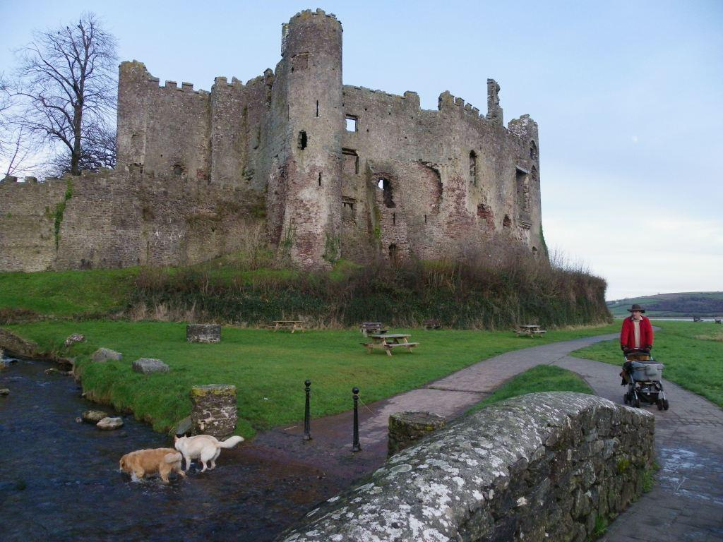 Laugharne Castle with dogs paddling in stream