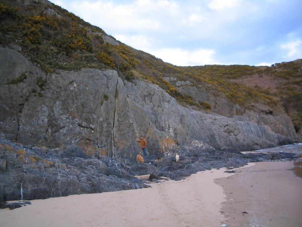 Oxwich Bay Dog Walks man touches rock cliff at end of bay