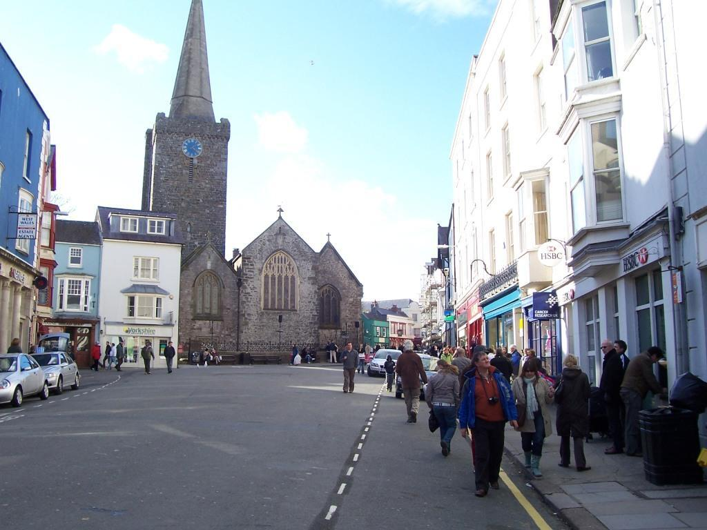 Tenby Town church clock tower and people walking